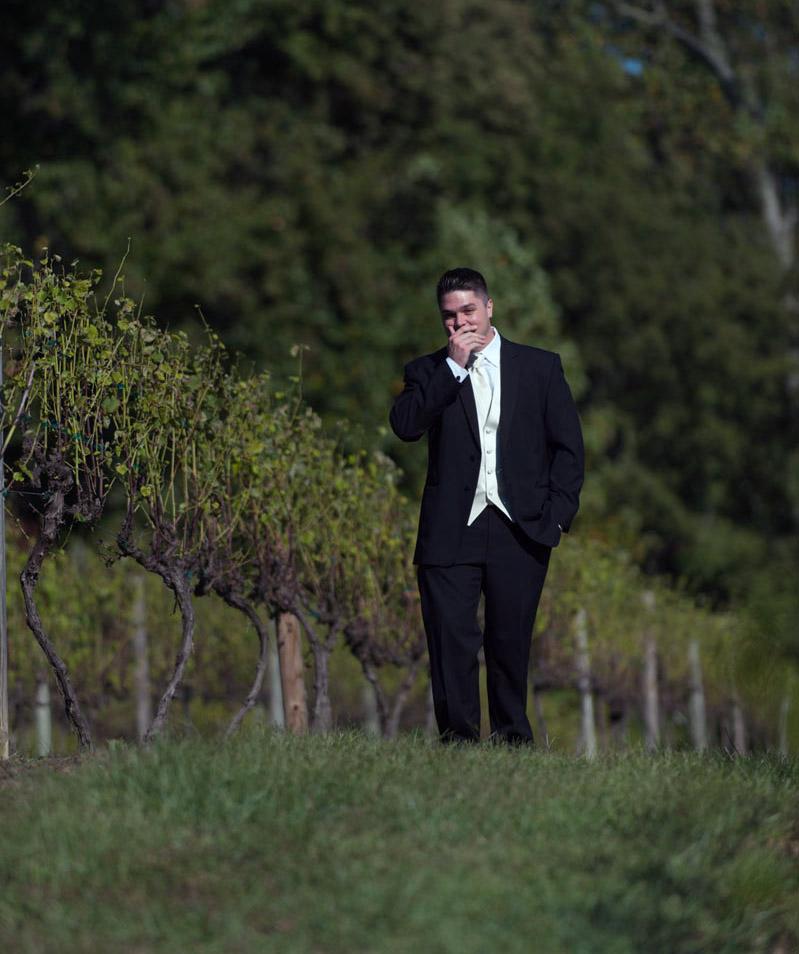 groom in tuxedo in a vineyard